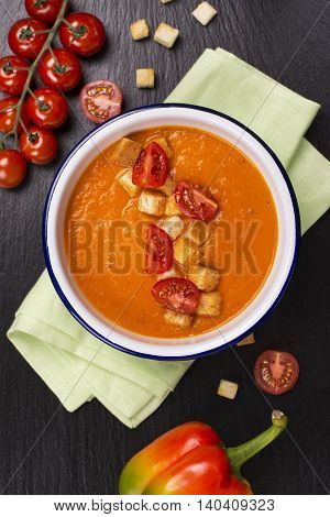 Tomato and carrot soup garnished with croutons over black stone table. Top view