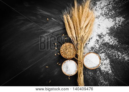 Wheat and flour on black background