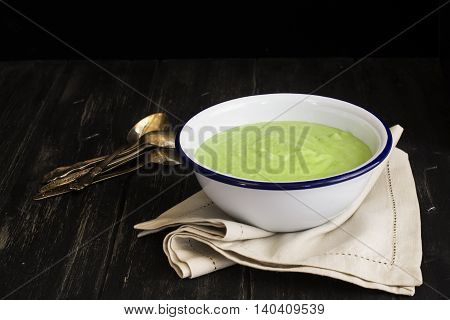 Green spinach and pea soup. Dark style. Selective focus. Space for text