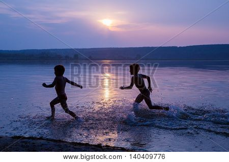 Silhouette of two boys running on river's beach against sunset