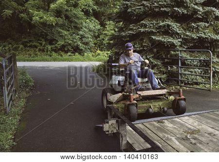 Man loading lawnmower on trailer on driveway in Virginia.