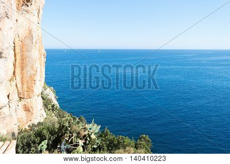 Sailboats And Orange Brown Vertical Rock
