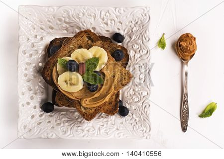Peanut butter sandwiches with bananas and blueberry. Top view. Space for text