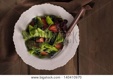 Raw food diet. Summer salad with berries and lettuce. Top view. Space for text