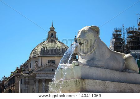 Rome Italy. Piazza del Popolo square lion fountain. The people s square has a public fountain in its center with four marble lions pouring water from their mouth.