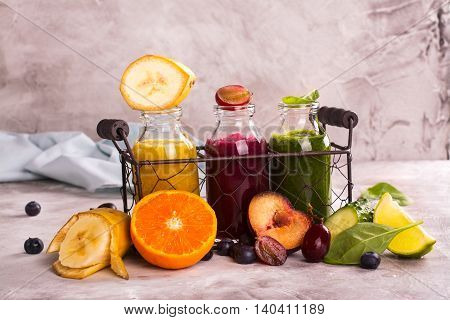 Fresh bright smothies in small bottles in a wire basket and ingredients over stone kitchen table. Toned image. Selective focus