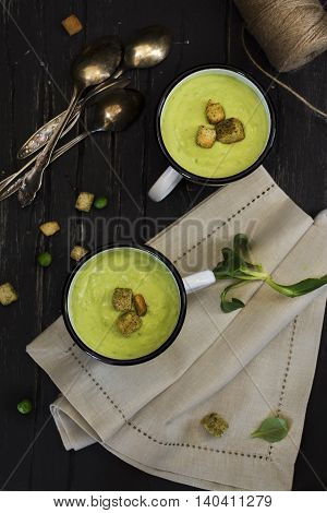 Green pea cream soup with croutons in enamel mugs over dark wooden table. Natural light