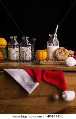 Xmas composition with milk and cookies for Santa Claus. Christmas card in dark tones. Selective focus