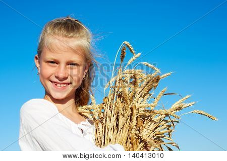 Child in white shirt holding wheat ears in the hands