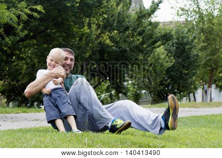 Laughing happy father and son are playing outdoors.