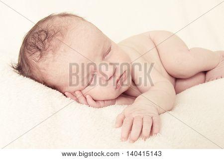 Newborn baby girl asleep on a blanket in vintage tones.