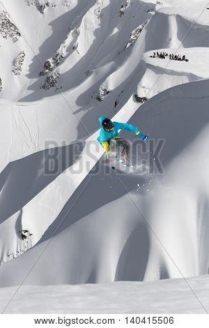 Snowboarder jumps on winter mountain.
