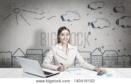 Attractive young businesswoman sitting at table and looking in camera