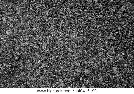 Closeup of dark grainy asphalt road texture