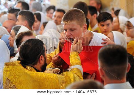 Orel Russia - July 28 2016: Russia baptism anniversary Divine Lutirgy. Young man taking Holy communion closeup