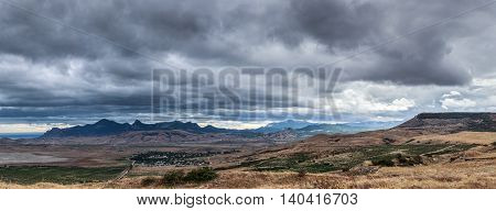 Running storm clouds on a background of mountains. Panorama