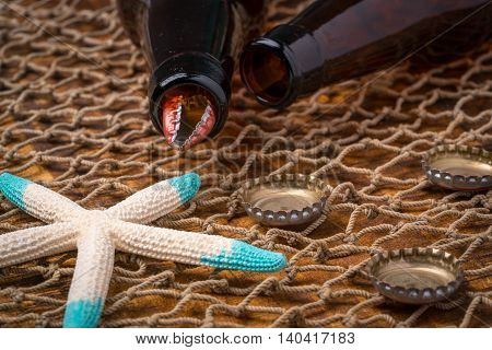 Empty beer bottles on a weathered table covered by a fishing net at the beach starfish in the background