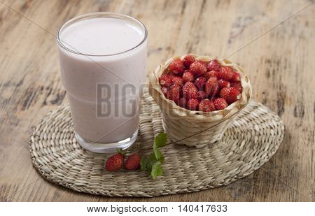 Smoothies with fresh strawberry with yogurt on a wooden table.
