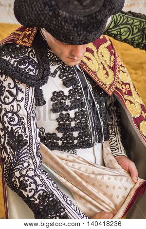 Andujar SPAIN - September 7 2014: Spainish bullfighter Miguel Abellan putting itself the walk cape in the alley before going out to bullfight typical and very ancient tradition in Andujar Spain
