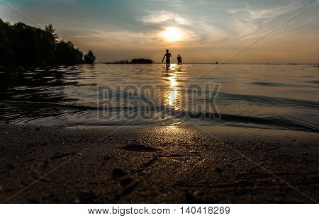 The son and the father go on the coast on a solar path after evening bathing.
