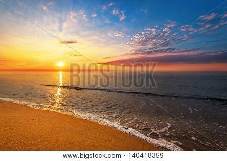 Brilliant ocean beach sunrise. Golden sands and blue sky.