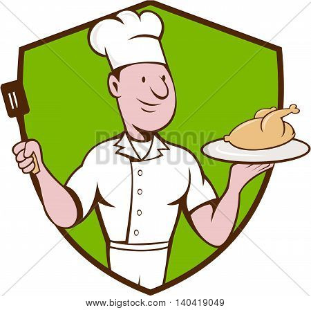 Illustration of a chef cook serving roast chicken on a platter on one hand and holding a spatula on the other hand viewed from front set inside shield crest on isolated background done in cartoon style.