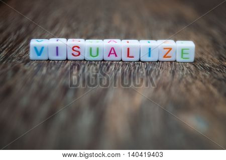 visualize word arranged from character cubes on wood table top. closeup. narrow depth of field.