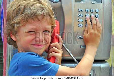 Small child talking by the public phone