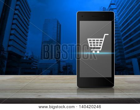 Shopping cart icon on modern smart phone screen on wooden table over city tower background Shop online concept