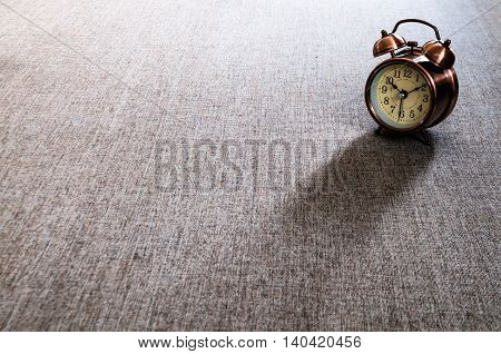 Bronze metalic retro style alarm clock on gray textile surface cushion.