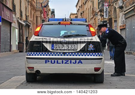 VALLETTA MALTA - FEBRUARY 28: Car of Malta police department and constable on the street of Valletta on february 28 2014. Valletta is a capital and the largest city of Malta.