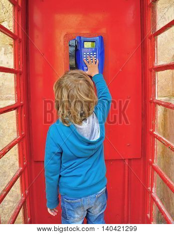 Small cute boy in the telephone box in british style