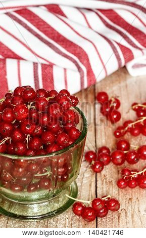 Juicy ripe red currant berries on a wooden table. Rustic style