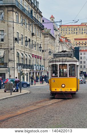 LISBON PORTUGAL - NOVEMBER 23: Yellow tram number 12 goes by the street of Lisbon city center on November 23 2013. Lisbon is a capital and must famous city of Portugal
