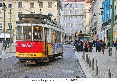 LISBON PORTUGAL - NOVEMBER 27: Red tram number 12 goes by the street of Lisbon city center on November 27 2013. Lisbon is a capital and must famous city of Portugal