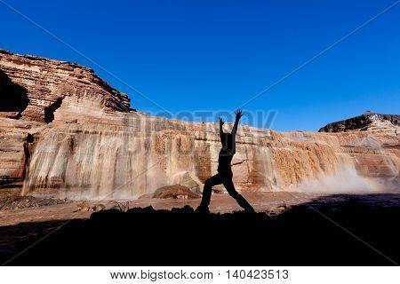 a woman practicing yoga at grand falls in northern arizona