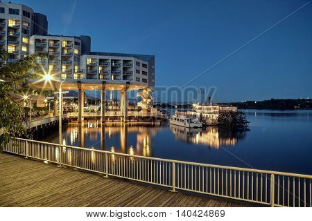 Hotel near the river evening illumination, paddle wheeler and restaurant