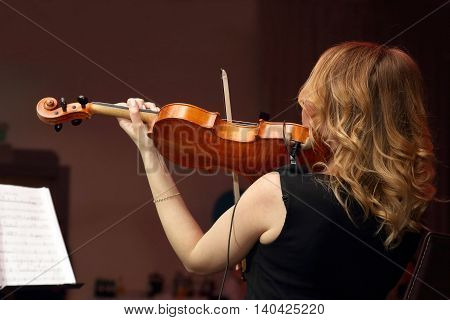 the a blonde woman plays the violin