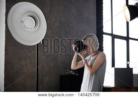 Girl photographer holding camera and photographs in the Studio