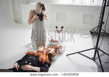 Girl photographer photographing fashion models in a clear coat with a pomegranate mask on the face and black clothes lying on white floor in Studio