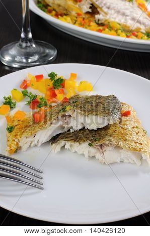 Slices of baked fish dorado with multi-colored pepper diced