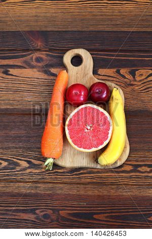 carrot, plum, grapefruit and banana on a wooden board on a wooden table. Set of fruits for fresh juice and smoothies