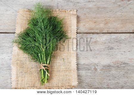 Fresh dill tied in a bun on a wooden surface and a napkin from jute cord and scissors