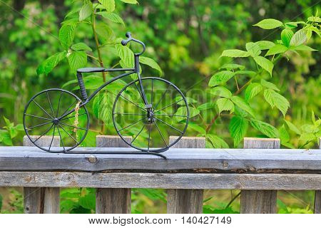 A little bicycle ornament made out of wrought iron on top of a wooden garden fence.