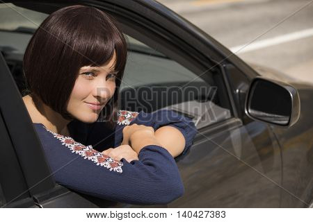 Young woman with burgundy hair looking out of right passanger window of car and smiling with front mirror