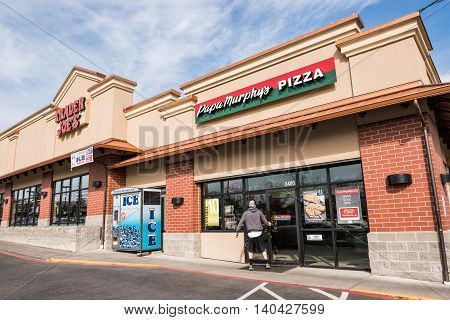 Bellingham, USA - April 3, 2016: Man entering Papa Murphy's Pizza restaurant next to Trader Joe's grocery store
