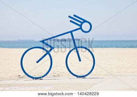 Bicycle bike rack made to look like a person riding a bicycle. Located along the coastline and city of Long Beach, California.