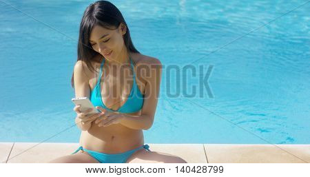 Young woman in a bikini reading an sms