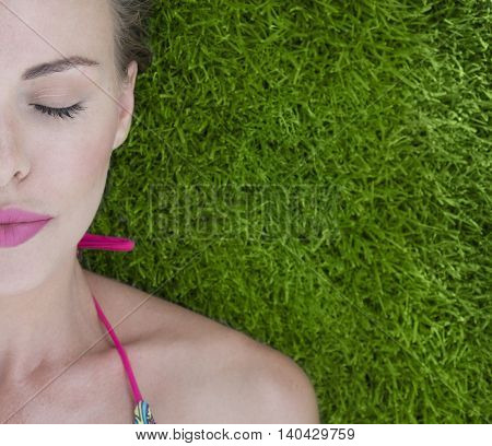 Closeup of pretty half face woman wearing bikini lying on a green grass on a sunny day