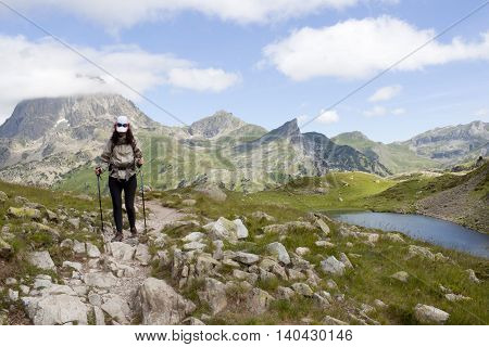 hiker woman between stones hiking in the middle of the mountains and a lake